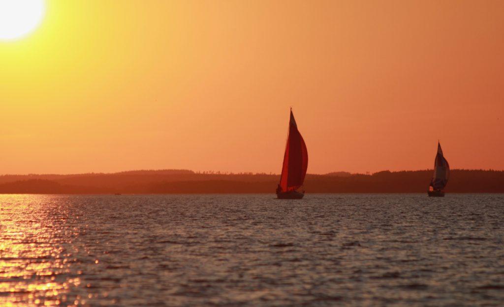 Kaksi purjevenettä ilta-auringon vastavalossa