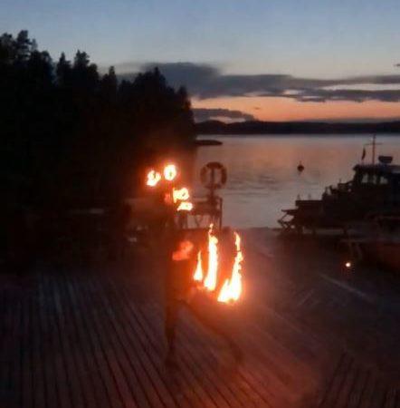 Järvimaisema auringon laskun jälkeen. Etualalla tulitaiteilijan tumma hahmo käsissään liekehtivät soihdut.