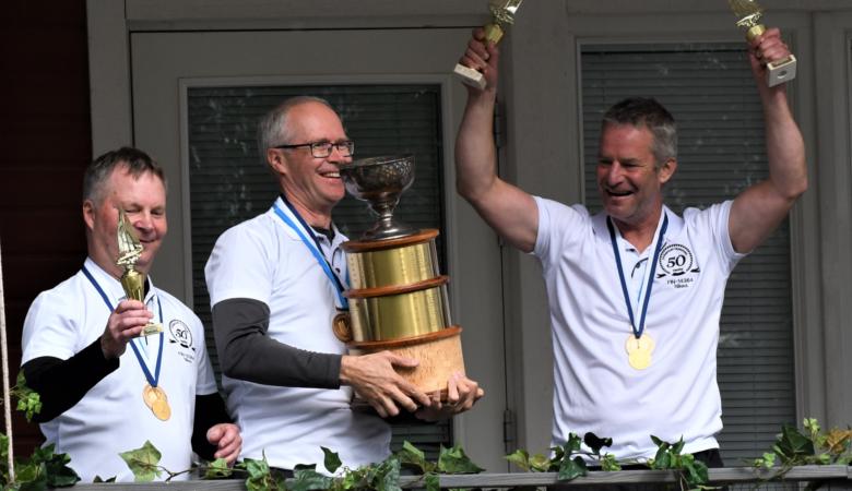 Kolme miestä voittopalkintojen kanssa.